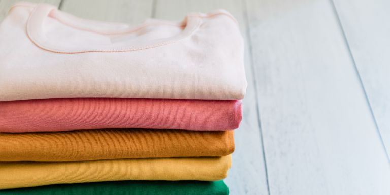 a stack of colorful tshirts on wood floor - GettyImages-1273553051