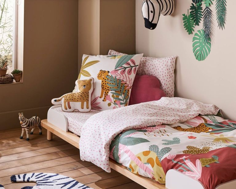 Vertbaudet kids bedding Pink Jungle set on bed in corner of beige room with lots of cushions and wall decal