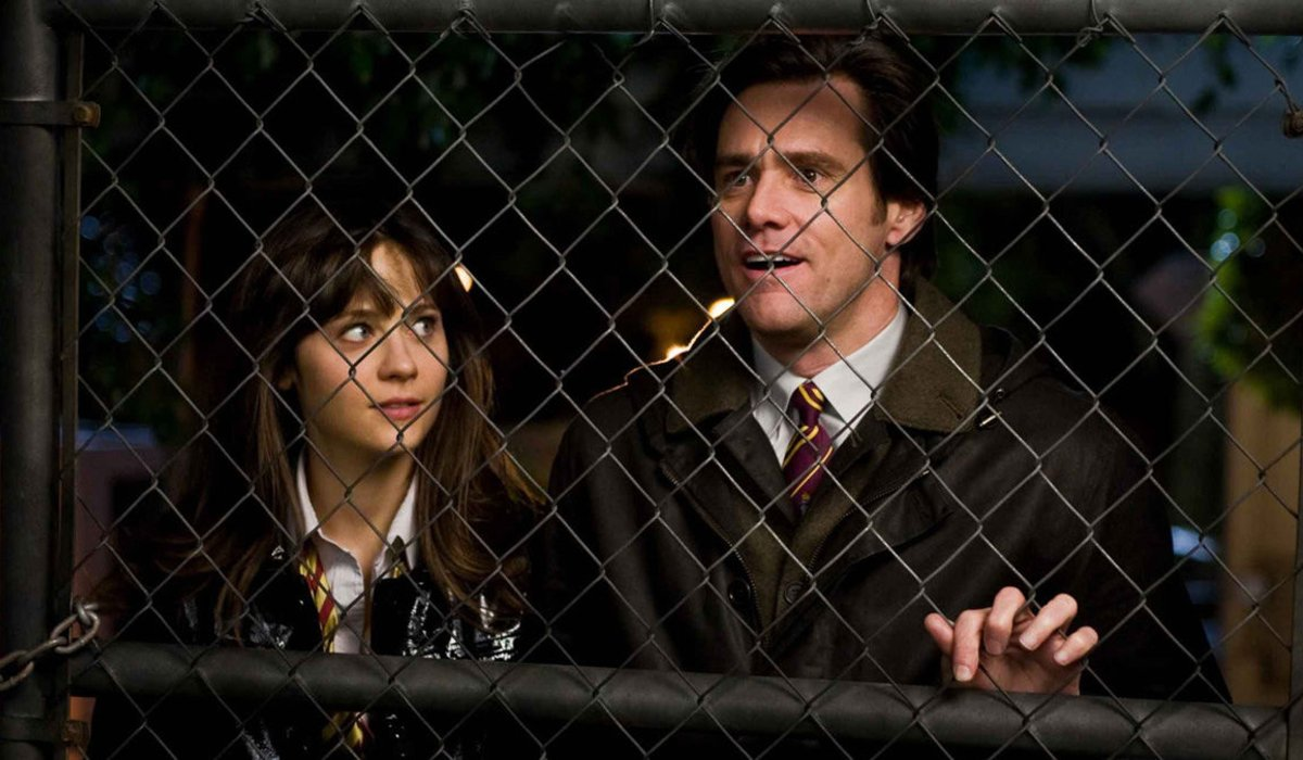 Zooey Deschanel and Jim Carrey stand behind an iron fence in Yes Man.