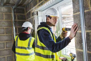 Builders fitting a window