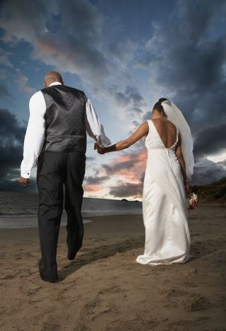 A newlywed couple walks on the beach.