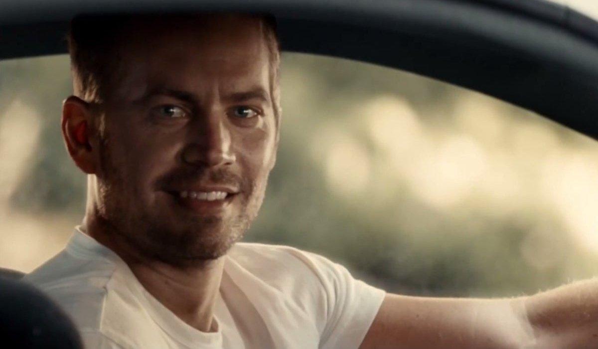 Paul Walker smiling behind the wheel in Furious 7.