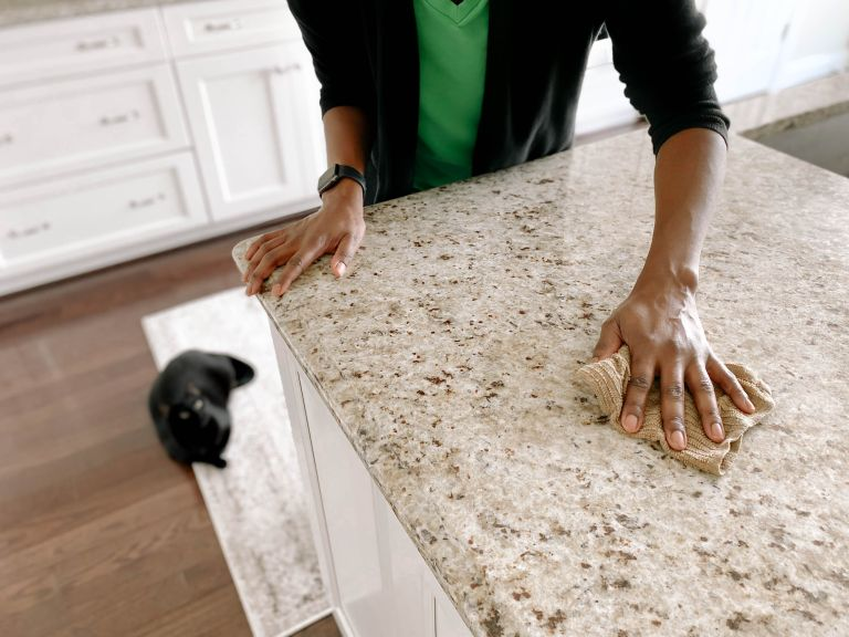 woman cleaning a granite countertop