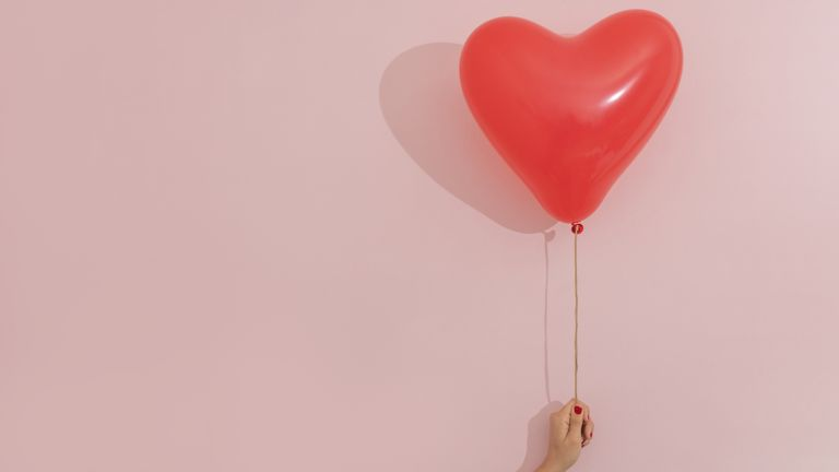red heart-shaped balloon on pink background