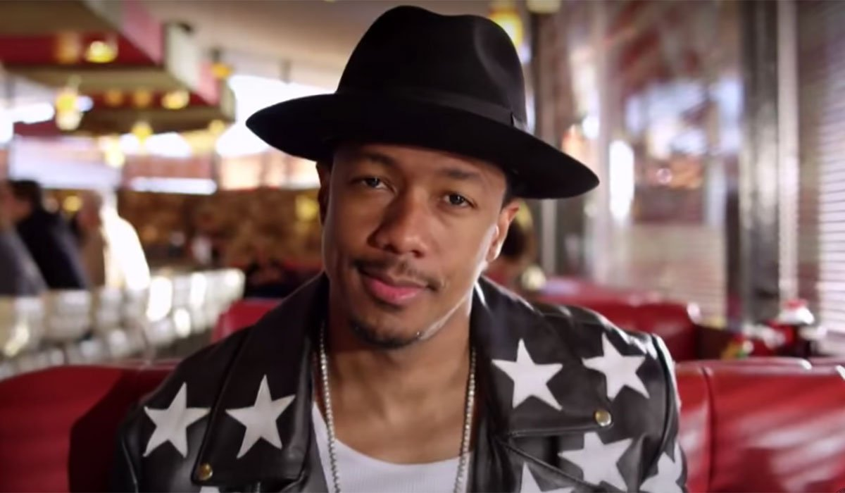 Nick Cannon looking cool in a hat and jacket inside a diner.