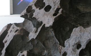 Surface detail of the Tomanowos meteorite, showing cavities produced by dissolution of iron.