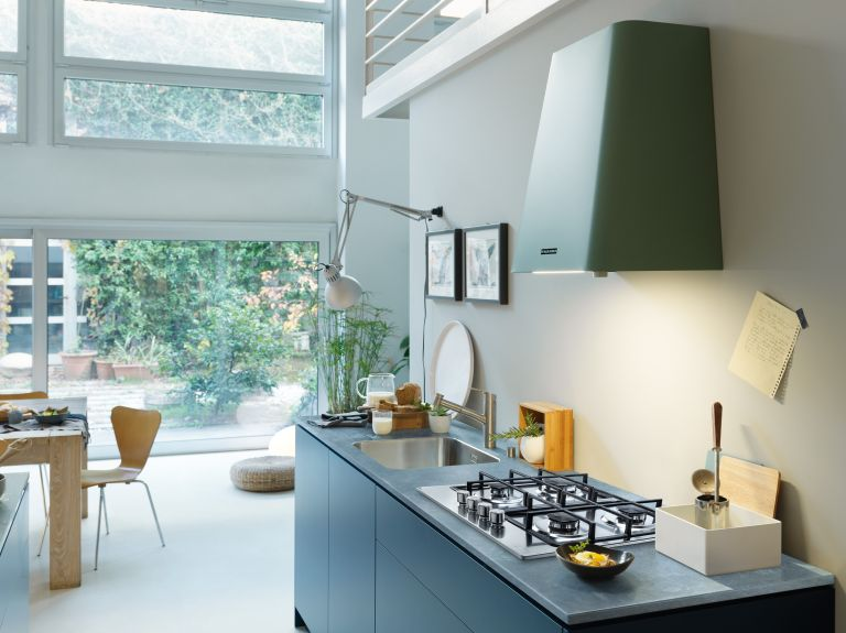 Cooker hood: modern open plan kitchen diner with a green cooker hood and blue handleless cabinets