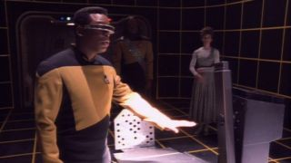 Laforge from Star Trek The Next Generation on the holodeck with hand hovering over a desk.