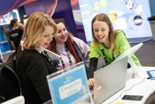 Smiling Bett attendees look at something interesting on a laptop computer