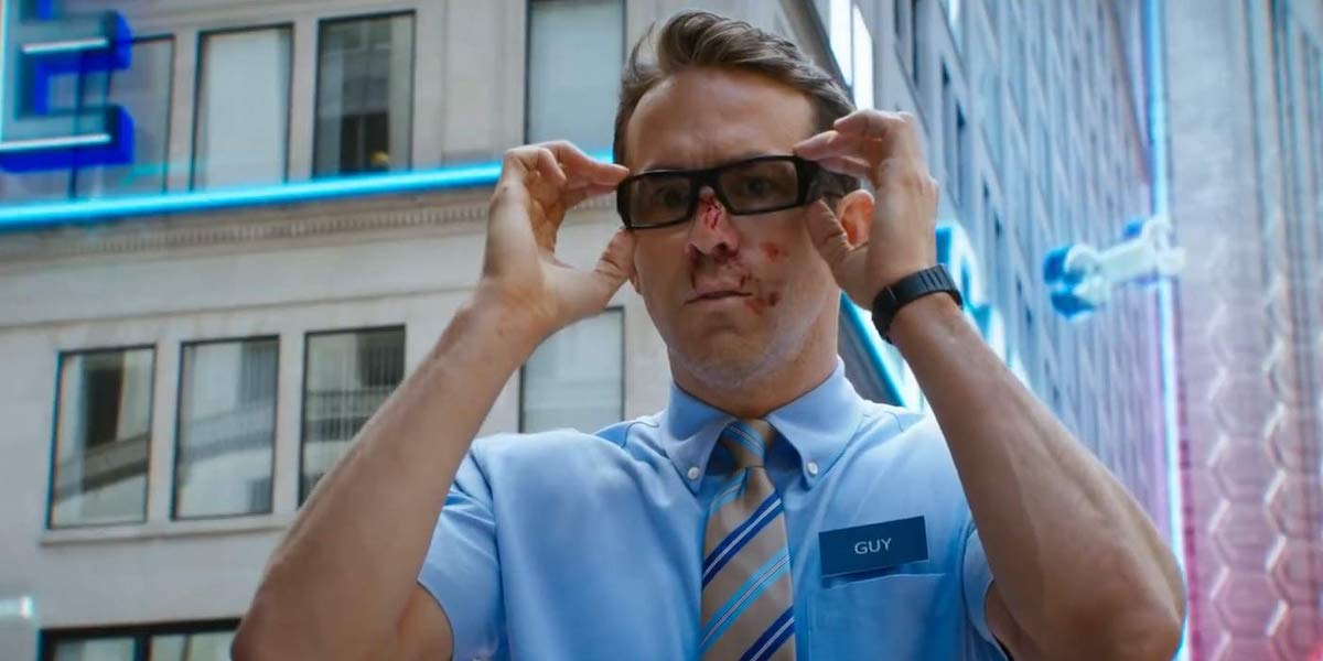 Guy (Ryan Reynolds) has a bloody face as he puts on his glasses in 'Free Guy.'