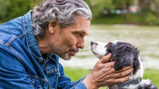 Can dogs understand humans? Man holding his dogs face on either side and looking into its eyes