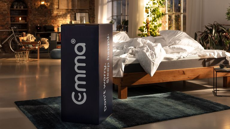 Emma mattress bed in a box packaged up and displayed next to a bed