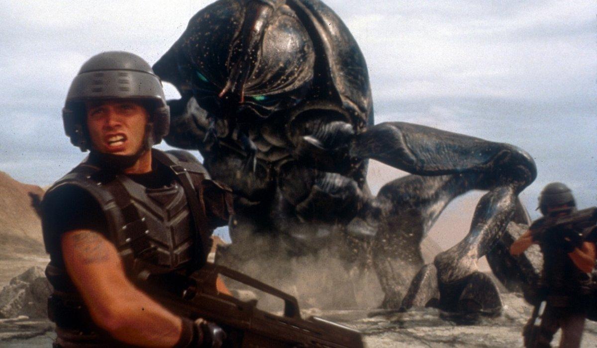 Starship Troopers Casper Van Dien looks away from a huge bug