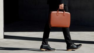Man holding a leather briefcase