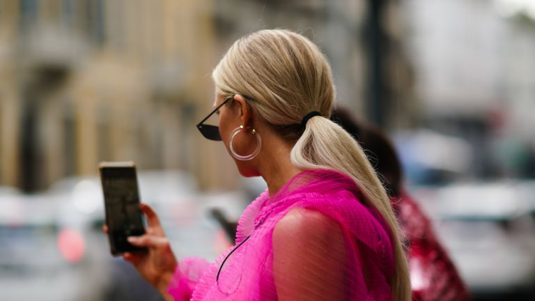 A guest wears earrings, sunglasses, a pink lace mesh dress, outside the Peter Pilotto show during Milan Fashion Week Spring/Summer 2020 on September 18, 2019 in Milan, Italy