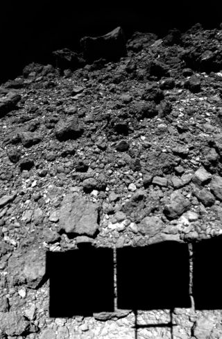 Hayabusa2 casts a shadow on the surface of the asteroid Ryugu during a landing maneuver.