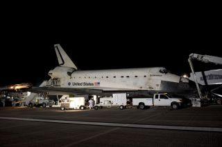 The landing convoy that will secure space shuttle Endeavour for towing to its processing hangar encircles the vehicle landing on the Shuttle Landing Facility's Runway 15 at NASA's Kennedy Space Center in Florida, on June 1, 2011.