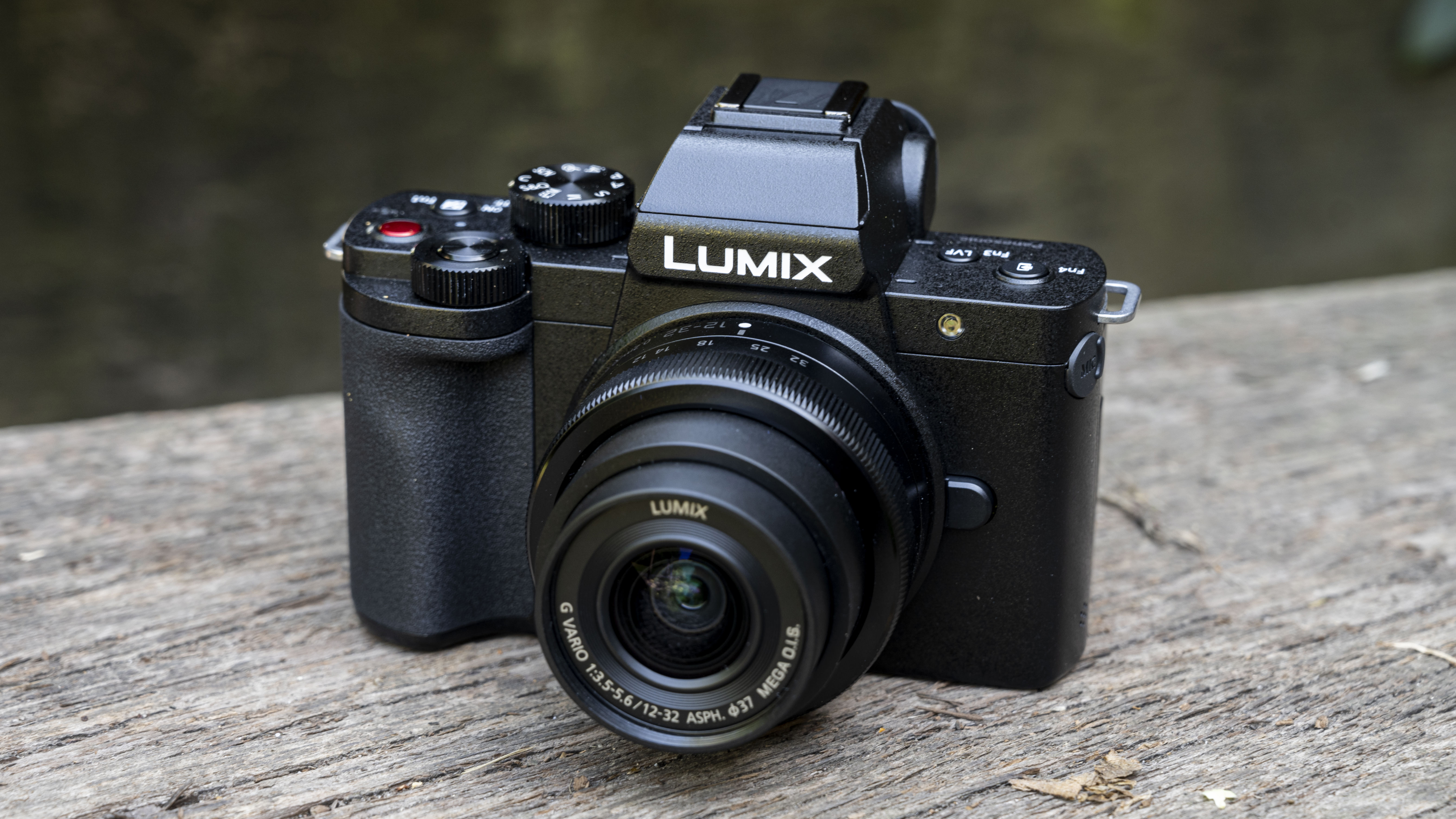 The Panasonic G100 placed on a wooden bench with its 12-32mm lens