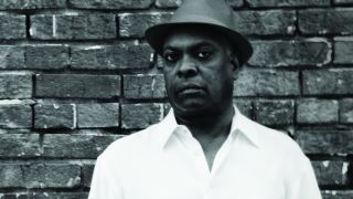 Booker T Jones standing in front of a brick wall.
