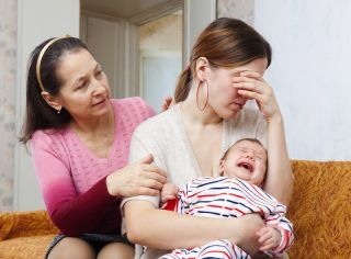 A woman cries while holding a baby, while an older woman looks on and tries to offer comfort.