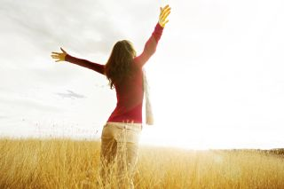 A woman raises her arm to greet the sun with joy.