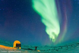 National Geographic photographer Mike Theiss taking in the northern lights. The sign marks the edge of the Arctic Circle can be seen to the left.