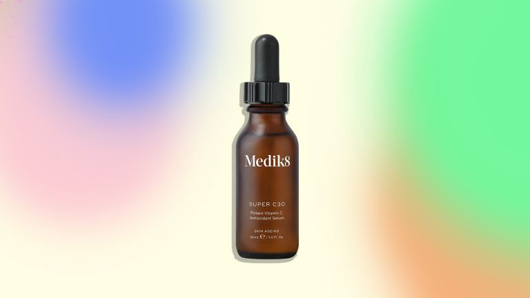 An image of the Medik8 Super C30 serum on a colorful background