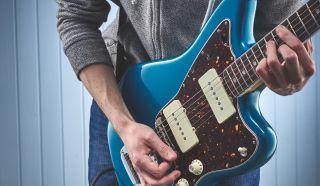 A man plays a blue Fender Jazzmaster
