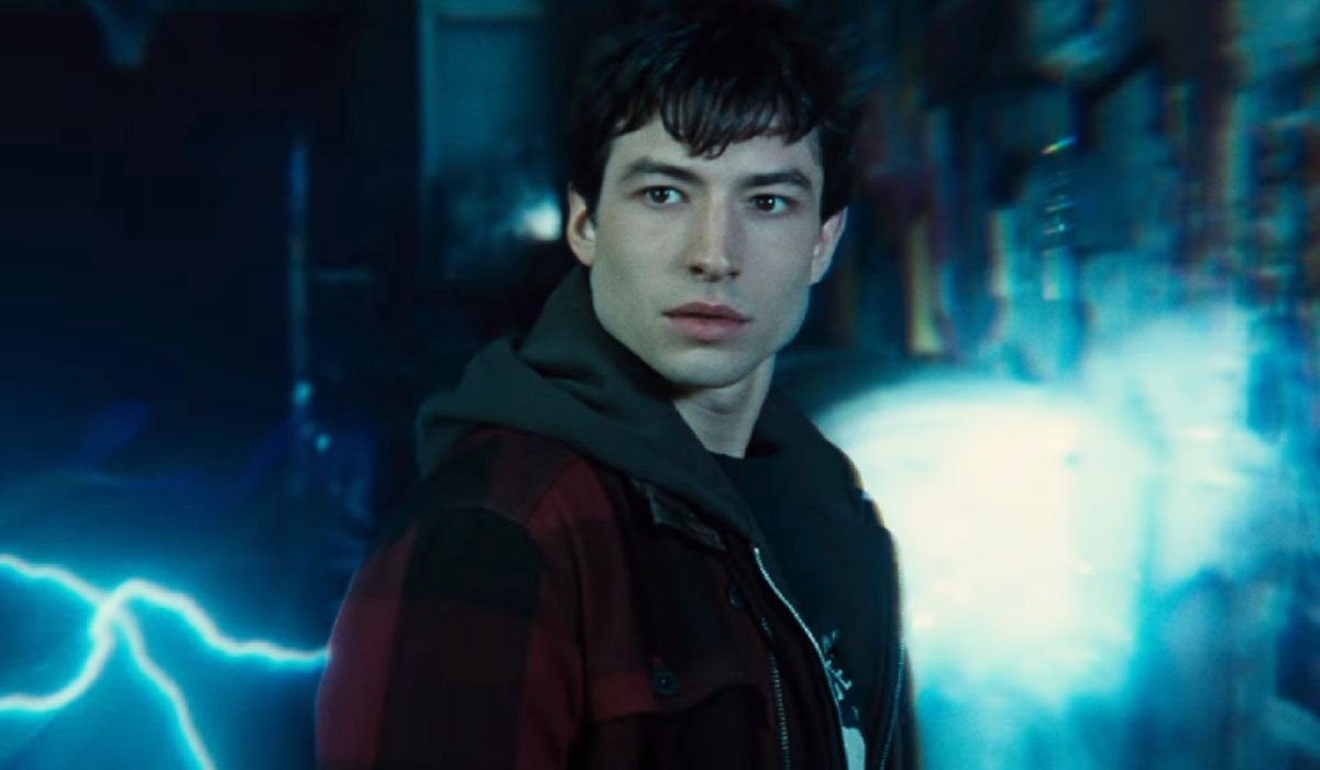 Ezra Miller staring straight ahead with lightning behind him.