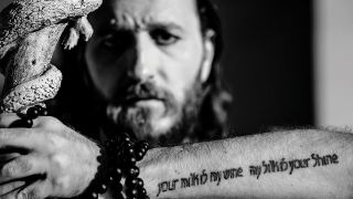 a portrait of kobi garhi holding his tattooed arm up to the camera