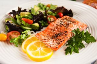 salmon steak on a plate with salad