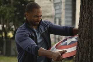 Sam Wilson (Anthony Mackie) attempts to remove Captain America's shield after getting it embedded in a tree