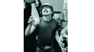 Angus Young of AC/DC holding a milk bottle