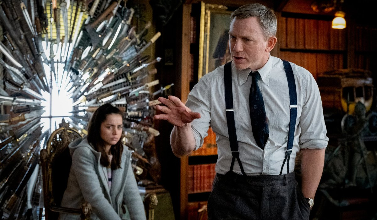 Knives Out Ana de Armas sitting in the knive throne listening to Daniel Craig tell a story