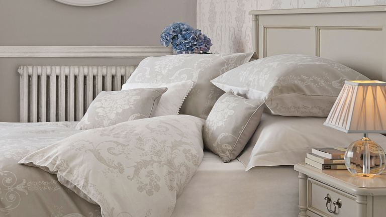 dove grey bed frame with grey printed bed linen, round mirror and bedside table with lamp - Laura Ashley
