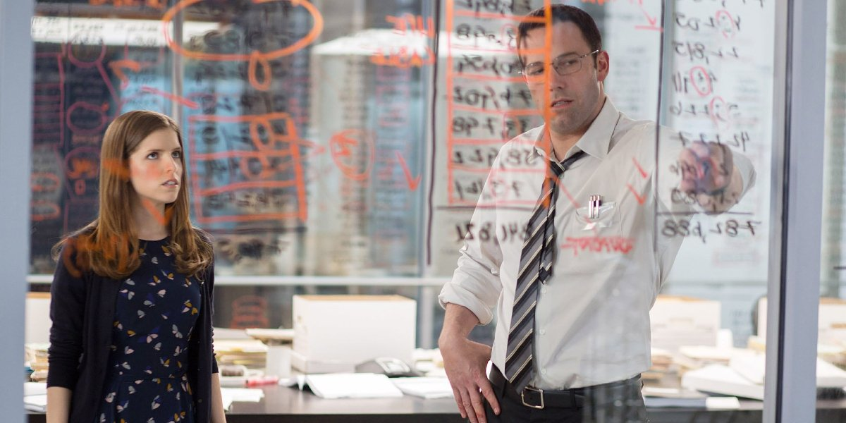 The Accountant Anna Kendrick and Ben Affleck looking over numbers on the wall