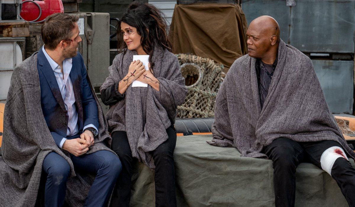 Salma Hayek smiles at Ryan Reynolds, next to a confused Samuel L. Jackson in The Hitman's Wife's Bodyguard.