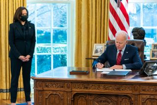 President Joe Biden, joined by Vice President Kamala Harris, signs two executive orders on healthcare Thursday, Jan. 28, 2021, in the Oval Office of the White House.