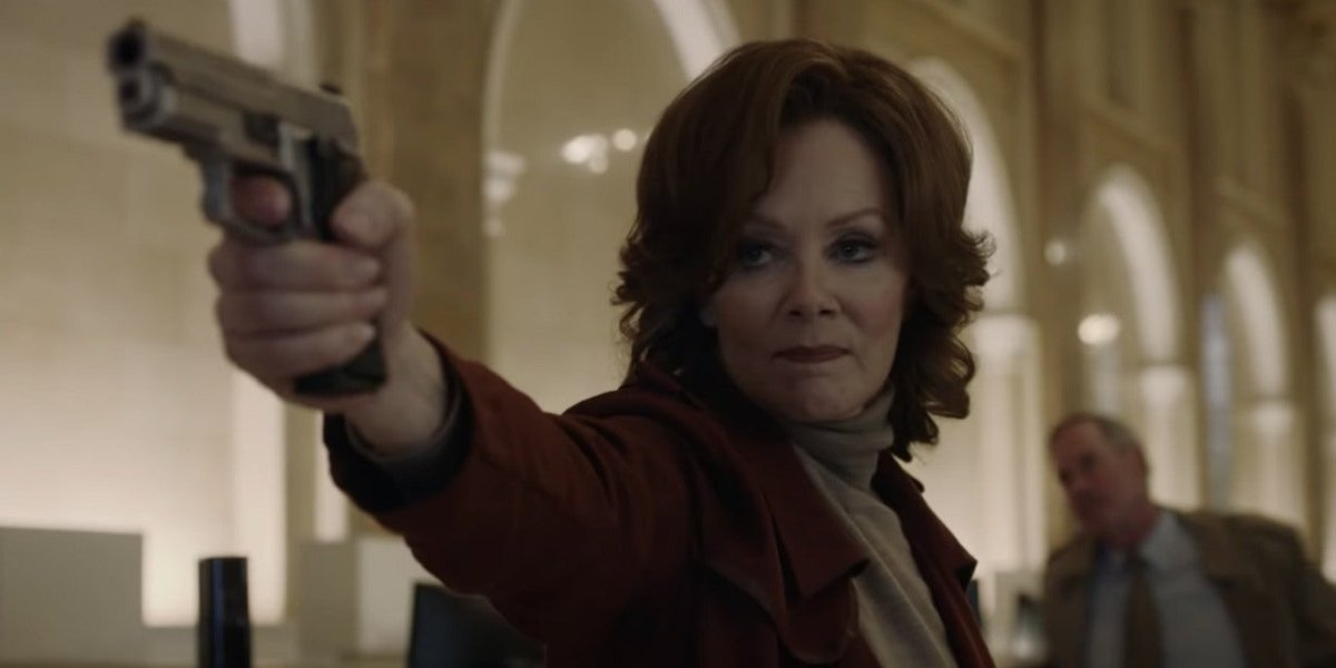 Jean Smart aiming her gun in a bank in Watchmen.