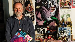 A photo of Brian Bolland sat with his records and illustrations in the background