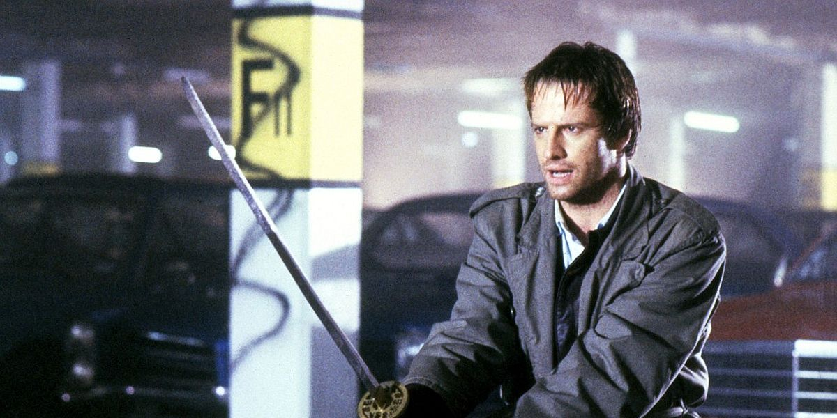 Christopher Lambert holding a sword in a parking garage in Highlander