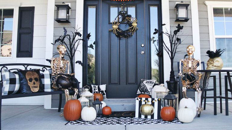 fall front porch ideas using gold skeletons and pumpkins