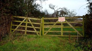 Private land sign on wooden gate