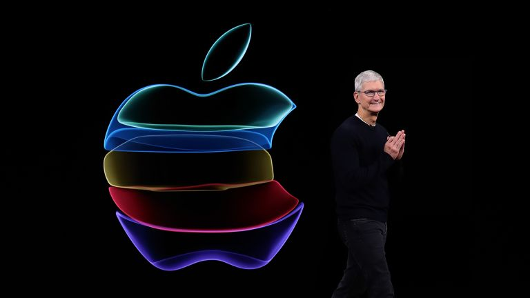 Tim Cook presenting during an Apple keynote, on black background, with multicoloured Apple logo beside him
