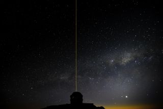 The Gemini South telescope in Chile is seen, laser blazing, during laser operations using the Gemini Multi-conjugate adaptive optics System (GeMS).