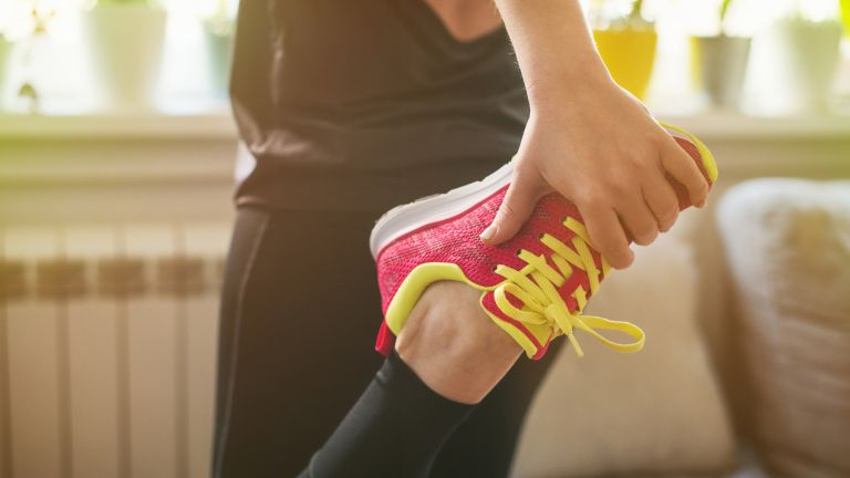 Woman stretching with a workout shoe