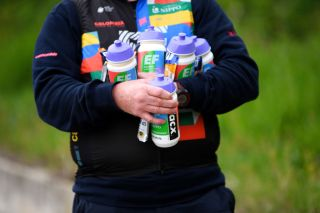 An EF Education-Nippo soigneur waits with bidons for riders in the Giro d'Italia