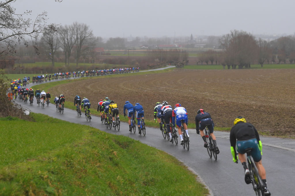 NOKERE BELGIUM MARCH 17 The peloton during the 75th Nokere Koerse Danilith Classic 2021 Mens Elite a 1955km race from Deinze to Nokere Rain Fog Landscape NokereKoerse on March 17 2021 in Nokere Belgium Photo by Luc ClaessenGetty Images