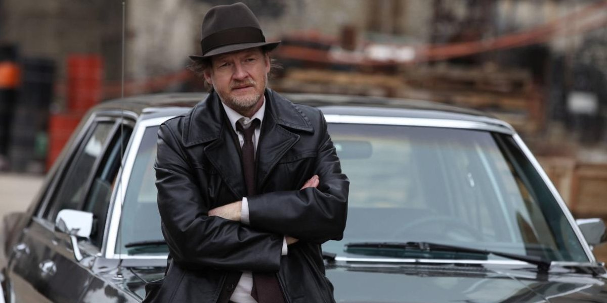 Gotham Donal Logue sits, arms crossed, on the hood of his car