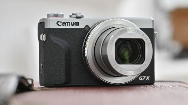 A powered-on Canon PowerShot G7 X Mark III perched on a leather sofa